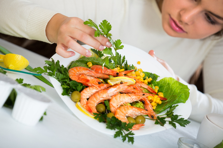 Brunette girl decorating fried fish with herbs on plate Stock Photo