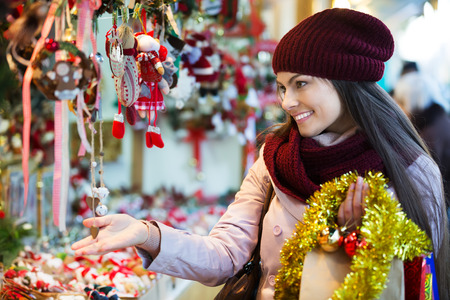 Young smiling woman shopping at festive fair before Christmas