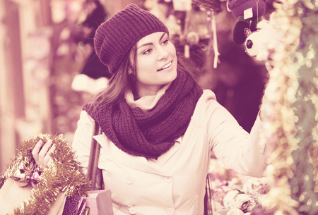 overspending: Portrait of female customer near the counter with the Christmas gifts