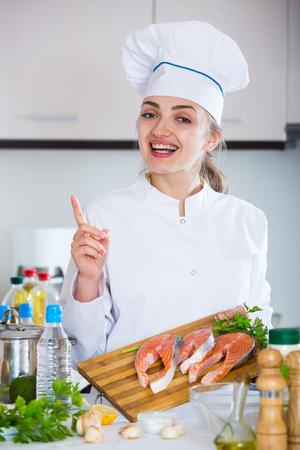 jorobado: Positivos femeninos cocinero que sostienen los filetes de salmón en tajadera