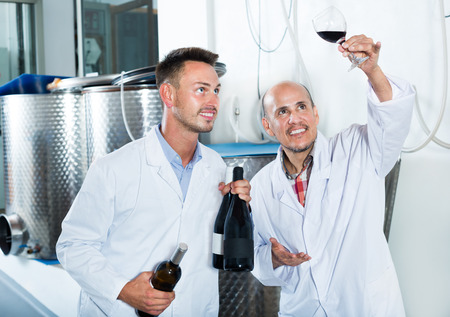 Happy two factory workers in the uniform standing together and examining sample of wine in the glass. Focus on young man