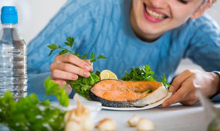 jorobado: chica en suéter azul sonriendo con salmón preparado en la cocina