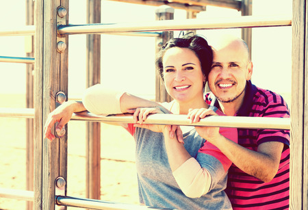 wall bars: Portrait of mature man and woman standing together close to wall bars and smiling