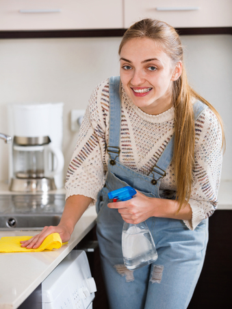 householder: Portrait of positive smiling  housewife cleaning with supplies in kitchen