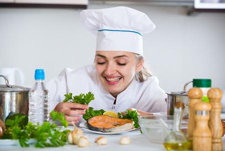 jorobado: cocinero de sexo femenino positivo que presenta con el filete de trucha en la cocina