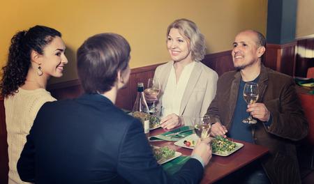 middle class: sonriendo positivo feliz a la gente de clase media que disfruta de la comida y el vino en el café