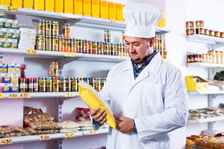 tinned goods: Salesman standing in food shop among grains and tinned goods Stock Photo