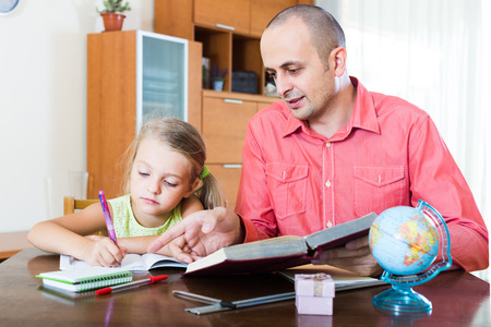 private room: Portrait of positive russian dad helping schoolgirl to study at home Stock Photo