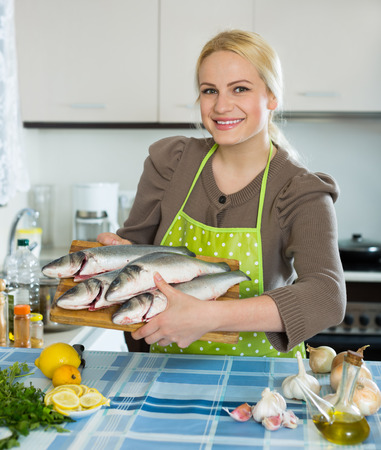 Happy girl holding raw fish in the home kitchen