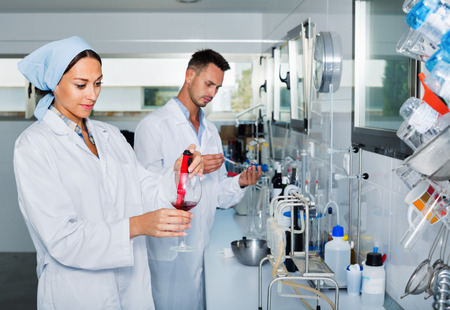 acidity: Two young efficient smiling  researchers in white coat checking wine acidity and sugar saturation in chemical laboratory Stock Photo