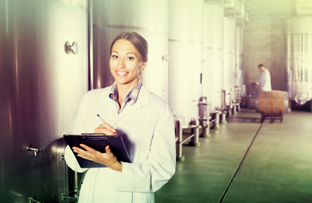 Young woman standing with cardboard in hands in fermentation compartment on factory