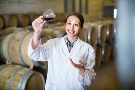 Cheerful efficient woman wearing coat holding glass of wine in large cellar on winery factory