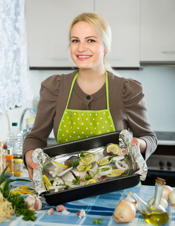 Happy smiling blonde housewife cooking fish at home kitchen