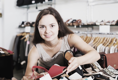 Cheerful young brunette buying summer shoes in shoes center