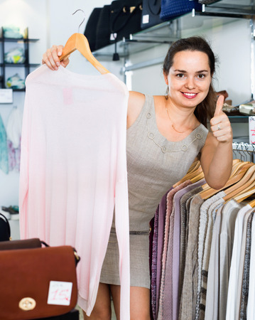 Smiling woman choosing new long sleeve blouse in apparel shop Stock Photo