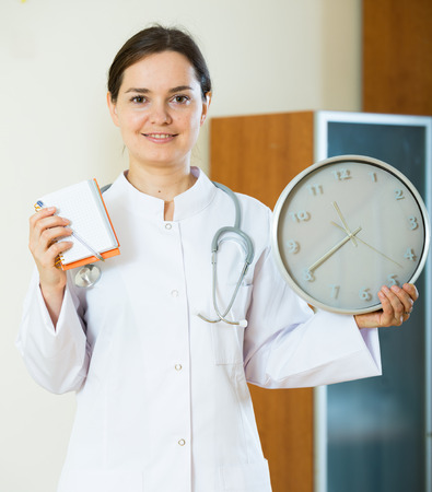 Portrait of professional female family doctor with big clock