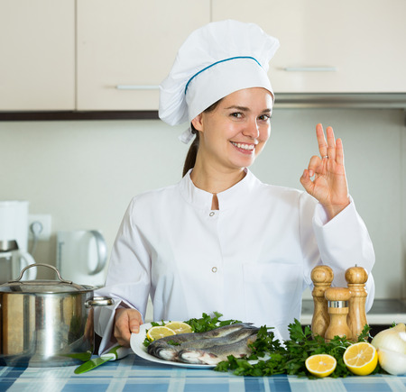 cartilaginous: Smiling young female chef working with fish in kitchen