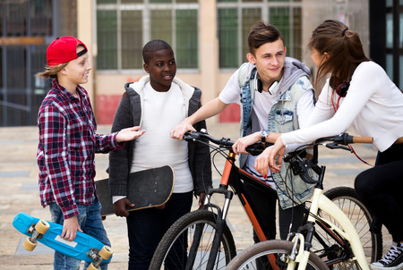 blabbing: Attractive four teenagers with skateboards posing in town square Stock Photo