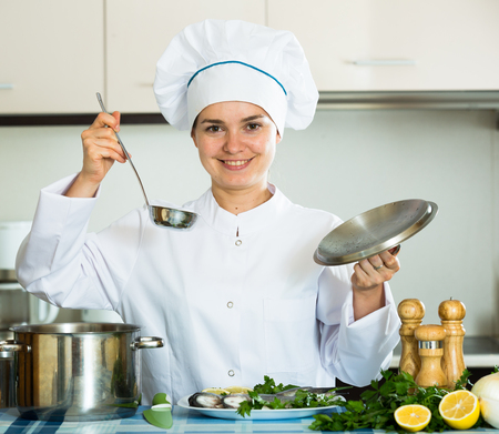 checking time: Happy young cook preparing atlantic fish and checking time Stock Photo