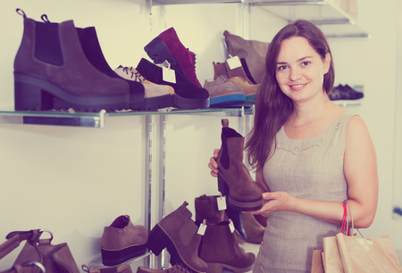 footgear: Portrait of young woman selecting loafers in footgear center