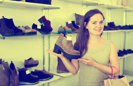 footgear: Portrait of positive female selecting loafers in footgear center