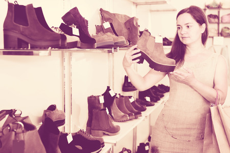 footgear: Portrait of adult female selecting loafers in footgear center Stock Photo