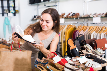 footgear: Portrait of smiling female customer selecting shoes in footgear center Stock Photo
