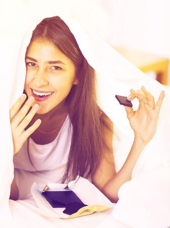 Muchacha sonriente en secreto comer chocolate en manta en la cama Foto de archivo