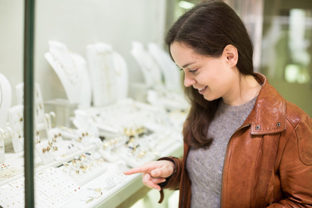 neckless: Smiling young woman customer admiring jewellery in display of boutique Stock Photo