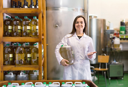 diligent: Portrait of diligent positive female posing with olive oil containers inside factory