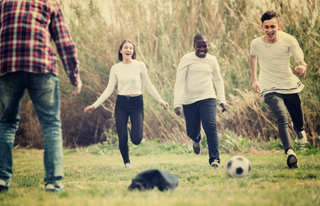 vehemence: Group of smiling  teenage friends playing football outdoors in autumn day