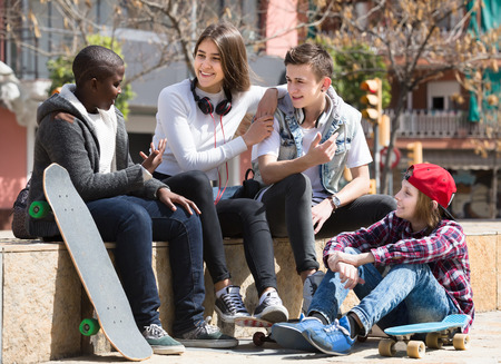 blabbing: girl and three young european boys hanging out outdoors and discussing something