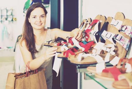 comprando zapatos: Happy jóvenes zapatos de verano morena de compra en el centro de los zapatos