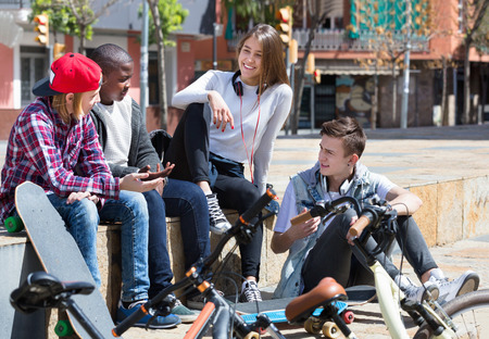 blabbing: Group of happy positive  teenage friends relaxing and chatting in town square