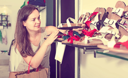 footgear: Portrait of woman customer selecting shoes in footgear center