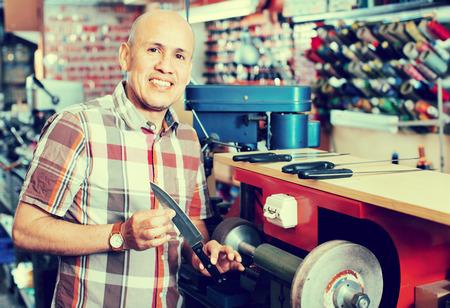Portrait of  positive elderly specialist sharpening steel knife on  wheel lathe