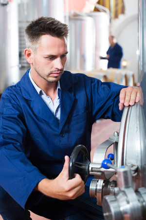 Man working on secondary fermentation equipment in winery manufactory Stock Photo