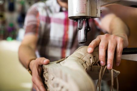 broaching: Shoemaker stitching footwear on machine in shoe atelier