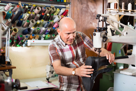 broaching: Mature workman sewing leather boots on stitch lathe in workshop