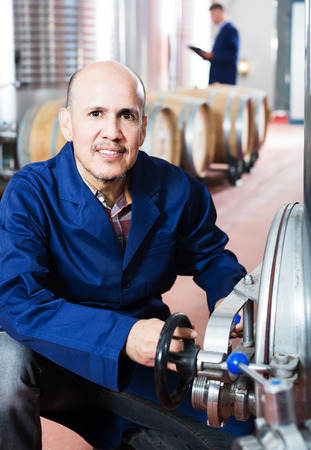 portret van lachende volwassen man aan het werk in de secundaire gisting sectie op wijnmakerij