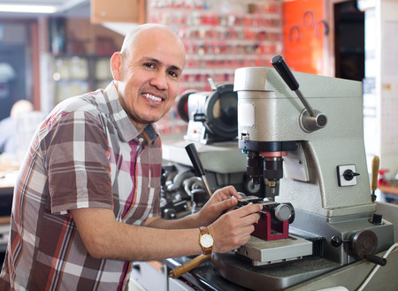 Joyful mature specialist making duplicates of keys on laser machine Stock Photo