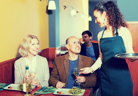 guests: Young waitress taking order at table with mature guests Stock Photo