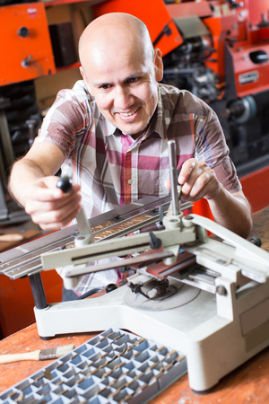 Professional worker making nameboard on printing system lathe in  interior