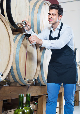 look latino: Happy glad man in uniform pouring red wine into glass in alcohol section with woods Stock Photo