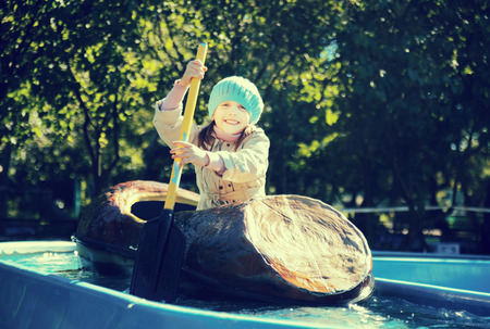 Smiling little girl swims by boat in amusement park