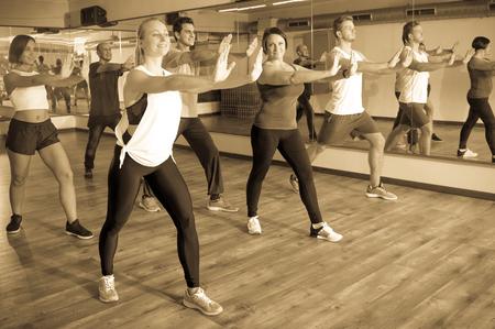 adult learners: Glad adultos que tienen clase de gimnasia grupo en el club deportivo