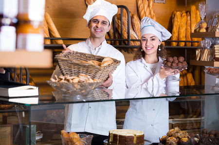 Hospitable man and smiling girl with delicious pastry at bakery display