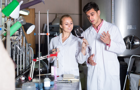 producing: Two laboratory technicians working with wine in cellar