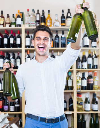 latino man buying bottle of wine in store with alcohol drinks