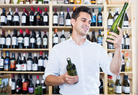 Smiling male wine expert holding wine bottles in winery section in store Stock Photo